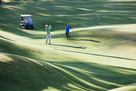 A young senior couple playing golf in the fairway of a golf course.の写真素材 [FYI02262394]
