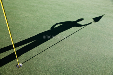 Shadow of golfers and the flag on a green of a golf course.の写真素材 [FYI02262417]