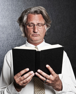 Studio portrait of Caucasian man actor holding and reading from a book.の写真素材 [FYI02262442]