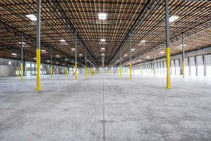 Wide angle interior view of large empty warehouse and loading dock doorsの写真素材 [FYI02262456]