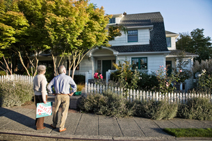 Hispanic seniors in front of their newly purchased remodelled older style home.の写真素材 [FYI02262459]