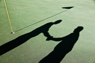 Shadow of golfers and the flag on a green of a golf course.の写真素材 [FYI02262460]