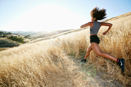 Young woman with curly brown hair running in urban park.の写真素材 [FYI02262479]