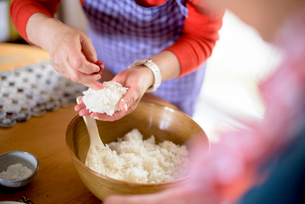 Close up of woman standing at a table in a kitchen, making sushi.の写真素材 [FYI02262486]