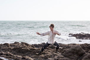 Young woman with brown hair and dreadlocks wearing white blouse standing on rocky shore by ocean, doの写真素材 [FYI02262498]