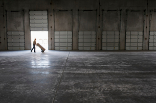 Man walking with loaded hand truck past loading dock doors in new empty warehouse.の写真素材 [FYI02262500]