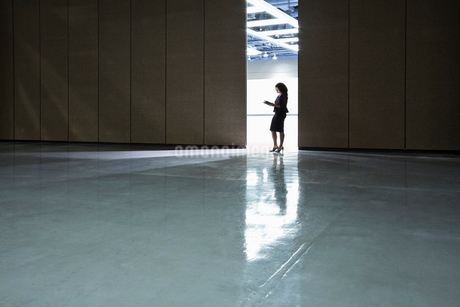 Businesswoman standing in a doorway between rooms in a convention centre arena.の写真素材 [FYI02262501]