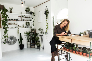Female owner of plant shop sitting at table, working on digital tablet, a selection of plants on wooの写真素材 [FYI02262504]