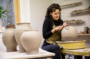 Woman with curly brown hair wearing apron working on spherical clay vase on pottery wheel.の写真素材 [FYI02262518]