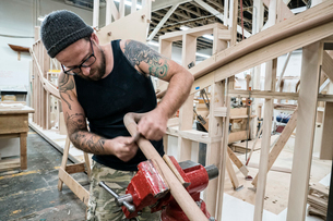 Caucasian carpenter working on a spiral staircase railing in a large woodworking shop.の写真素材 [FYI02262527]