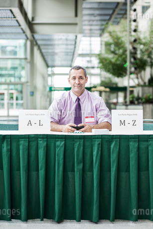 A Caucasian businessman working at registration desk in a convention centre.の写真素材 [FYI02262531]