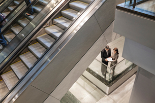 Two business people going over a report while standing next to a convention centre escalator.の写真素材 [FYI02262532]