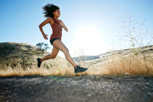 Young woman with curly brown hair running in urban park.の写真素材 [FYI02262546]