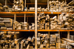 Large selection of wooden planks stacked on shelves in a warehouse.の写真素材 [FYI02262547]