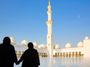 Rear view of two women holding hands, standing in front of mosque with white washed colonnade, minarの写真素材 [FYI02262557]