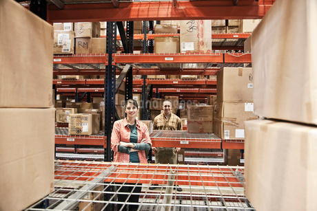 A Caucasian male and female warehouse workers surrounded by boxed products on racks in a distributioの写真素材 [FYI02262559]