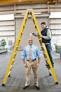 Black man factory owner and young Caucasian man factory worker goofing off together on the floor ofの写真素材 [FYI02262563]