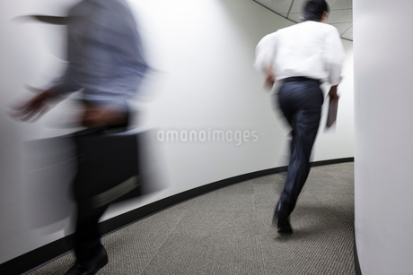 A blur of two businessmen running in an office hallway.の写真素材 [FYI02262573]