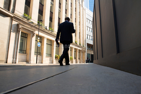 Low angle rear view of man wearing suit walking along urban street.の写真素材 [FYI02262589]