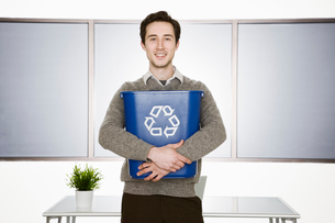 Caucasian businessman holding a recycle waste basket in his office.の写真素材 [FYI02262601]