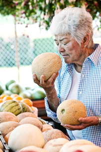 Senior woman standing at a farm stall, holding a fresh melon to her nose, smelling it.の写真素材 [FYI02262607]
