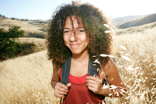 Young woman with curly brown hair hiking in urban park, smiling at camera.の写真素材 [FYI02262611]