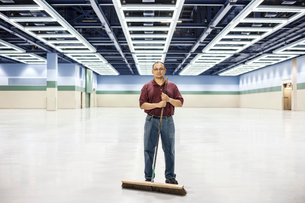 An Hispanic man standing with a broom in a large convention cener space.の写真素材 [FYI02262619]