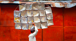 Side view of man carrying stack of metal containers on his head, walking past red metal wall.の写真素材 [FYI02262626]