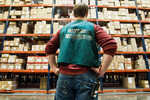 A view from behind a warehouse worker who is  checking inventory on the storage racks in a distributの写真素材 [FYI02262632]