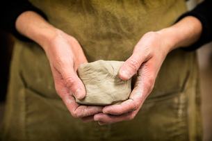 Close up of potter holding piece of pottery clay.の写真素材 [FYI02262636]