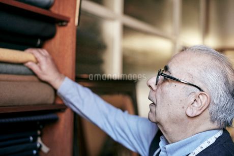 A man with grey hair and glasses reaching up to select fabrics from the choice of cloth.の写真素材 [FYI02262637]