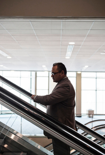 A Hispanic businessman checking his notebook computer while going up an escalator in a convention ceの写真素材 [FYI02262647]