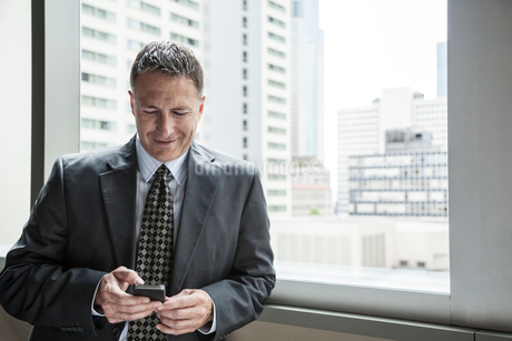 A Caucasian businessman texting on his phone while standing next to a window.の写真素材 [FYI02262650]