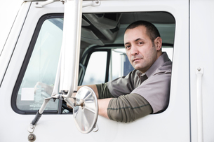 A portrait of a uniformed male truck driver in the window of his truck at a distribution warehouse.の写真素材 [FYI02262653]