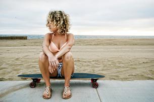 Young woman with curly blond hair wearing pink bikini sitting on skateboard on sandy beach.の写真素材 [FYI02262654]