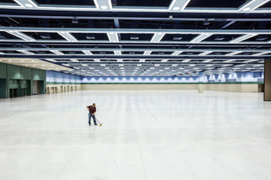 A lone man sweeping the floor of a convention centre arena area.の写真素材 [FYI02262659]