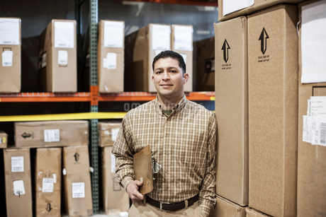 A Hispanic male warehouse worker standing next to racks of boxed products in a distribution warehousの写真素材 [FYI02262666]