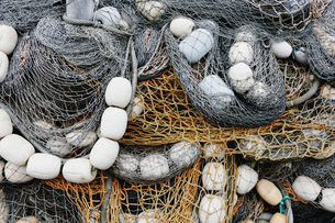 Fishing nets and floats, commercial fishing equipment in a heap on a quayside.の写真素材 [FYI02262670]