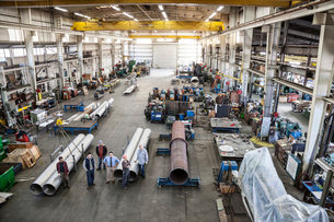 Mixed race team of workers and management people in a large sheet metal factoryの写真素材 [FYI02262681]