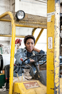 Black woman factory worker and a fork lift in a sheet metal factory.の写真素材 [FYI02262684]