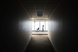 A businesswoman standing at a window at the end of a long hallway.の写真素材 [FYI02262688]