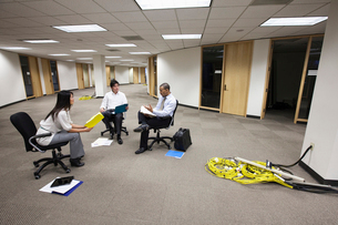 A mixed race group of three business people sitting in an open space and making plans for a new offiの写真素材 [FYI02262691]