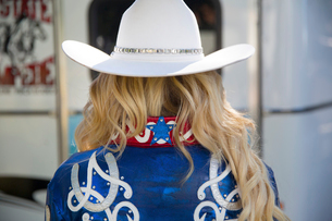 Rear view of woman with long blond hair wearing white Stetson hat and shiny blue jacket decorated wiの写真素材 [FYI02262693]