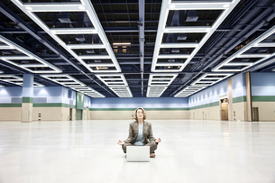A businesswoman in a yoga pose with a laptop computer in the middle of a convention centre arena.の写真素材 [FYI02262698]