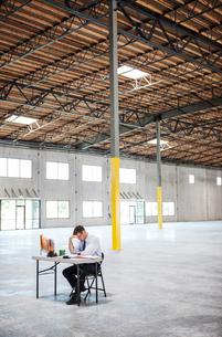 Caucasian man going over plans for new warehouse interior in front of loading dock doors.の写真素材 [FYI02262699]