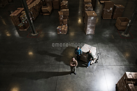 A group of three warehouse workers standing in the centre of a distribution warehouse.の写真素材 [FYI02262701]