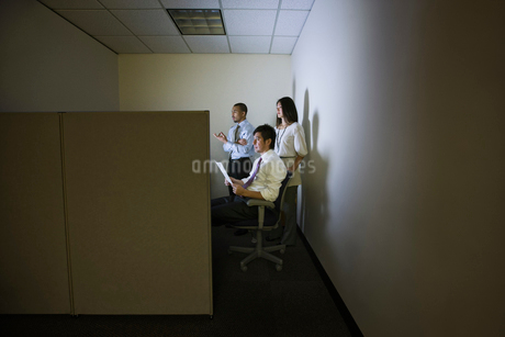 A mixed race group of three business people lit up by a desktop computer screen in a small corner cuの写真素材 [FYI02262710]