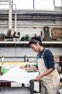Black woman factory worker going over project plans in a sheet metal factory.の写真素材 [FYI02262713]