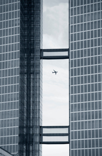 Passenger plane flying past two skyscrapers connected by elevated walkways out of glass.の写真素材 [FYI02262721]