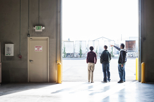 Three employees waiting for a product delivery while standing in a loading dock door at a distributiの写真素材 [FYI02262723]